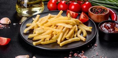 färska varma pommes frites med salt grönsaker och kryddor foto