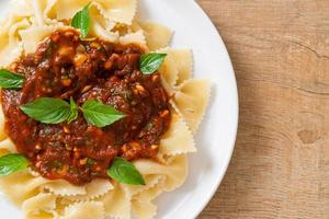 farfalle pasta med basilika och vitlök i tomatsås - italiensk sås foto