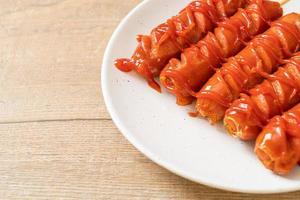 stekt korvspett med ketchup på en vit platta foto
