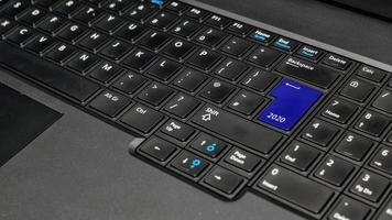 datoranteckningsbokstangentbord med blå 2020-tangent - semesterteknologikoncept foto