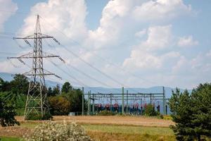 högspänningsstation på berg och bakgrund med blå himmel. foto