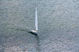 vit segelbåtmodell som flyter i sjön. foto