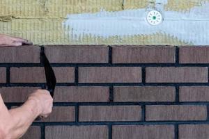 murarearbetare som installerar tegelstenar på byggarbetsplatsen. foto