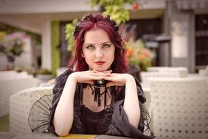 ung underbar rödhårig kvinna som sitter i ett utomhuscafé klädd i retromodekläder. foto