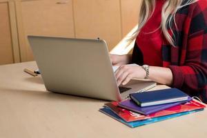 blond kvinna sitter vid en bärbar dator och skriver. det finns en bärbar dator, en surfplatta, en telefon och en bärbar dator på bordet. foto