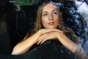 en ung, vacker kvinna med långt hår sitter vid ratten på bilen och tittar drömande genom bländningen på den främre vindrutan. foto
