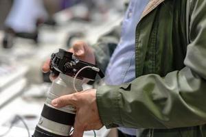 en man i en butik provar en ny fotokamera. foto