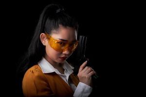 asea kvinna som bär en gul kostym en hand som håller en pistol på svart bakgrund foto
