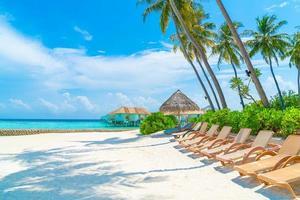strandstolar med tropisk Maldiverna östrand och hav - bakgrund för semestersemesterbakgrund foto