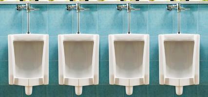 rad med vita pissoarer i manliga toaletten foto