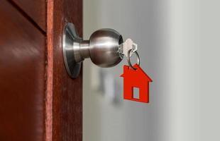 öppen dörr med nycklar, husnyckel i nyckelhålet med litet hus foto