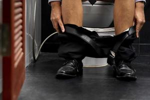 affärsman som sitter på toaletten foto