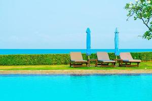 stolbassänger eller sängar och paraplyer runt poolen med havsbakgrund - semester och semesterkoncept foto