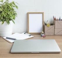 bärbar dator med kontorsmateriel på bordet. foto