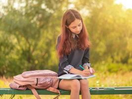 flicka tonåring skolflicka skriver i en anteckningsbok som sitter på en bänk. foto