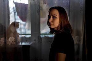 porträtt av en ung tonårsflicka i hennes rum på kvällen. röd katt vid fönstret, silit på fönsterbrädan foto