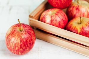 närbild av färska mogna röda äpplen i en trälåda. foto