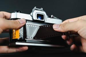fotograf hand laddar 35 mm film i slr film kamera. foto
