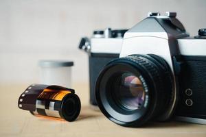 gammal slr-filmkamera och en filmrulle på träbakgrund. foto