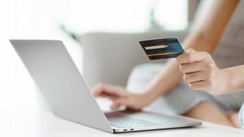 ung kvinna med kreditkort och använder bärbar dator. online shopping, internetbank, e-handel, spendera pengar, arbeta hemifrån koncept foto