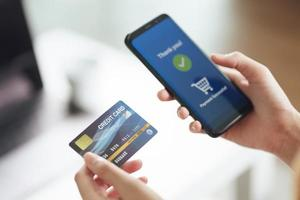 ung kvinna som rymmer kreditkort och använder smart telefon för online-shopping, internetbank, e-handel, spendera pengar, arbeta hemifrån koncept foto