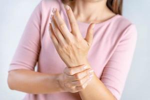 närbild ung kvinna håller sin handled på vit bakgrund. handskada, smärta. hälso- och sjukvårdskoncept. foto