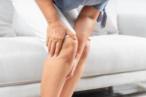 närbild av knubbig kvinna som sitter i soffan och känner knäsmärta och hon masserar knäet. hälso- och sjukvårdskoncept. foto