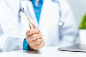 läkaren håller medicinsk kvicksilvertermometer på sjukhuset. sjukhusverktyg, utrustning. hälso- och sjukvårdskoncept. foto