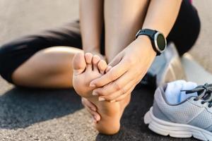 löpskada ben olycka - sport kvinna löpare skadar håller smärtsamma stukad fotled i smärta. kvinnlig idrottare med led- eller muskelsårighet och problem med ont i underkroppen. foto