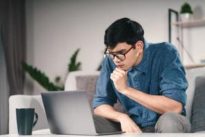 fundersam eftertänksam allvarlig asiatisk man i glasögon tittar på bärbar datorskärm och tänker efter lösning för att lösa problemet. foto