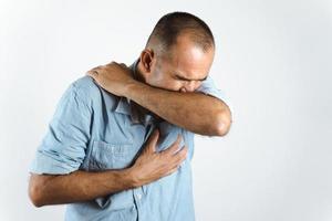 man nyser eller hostar i armbågen för att förhindra spridning av viruset covid-19 eller koronavirus på vit bakgrund. foto