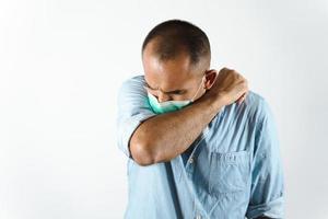 man som bär ansiktsmask som nyser eller hostar i armbågen för att förhindra spridning av viruset covid-19 eller koronaviruset på vit bakgrund. foto