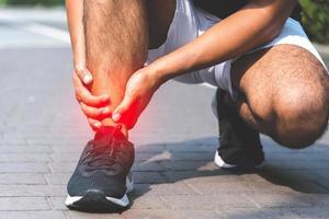 trasig vriden fotled. löpare vidrör foten i smärta på grund av stukad fotled foto