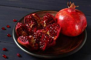 två granatäpplen på gammalt rustikt bord stilleben i mörka toner foto