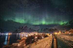 aurora borealis över skandinavisk by ljus skiner på vintern foto