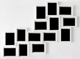vit bildram och svart dekorativt hängande på vit vägg foto
