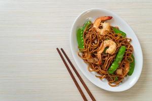 uppstekt yakisoba nudlar med gröna ärtor och räkor - asiatisk matstil foto