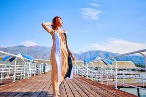 kvinna på piren i lång klänning foto