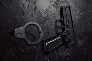 pistol och handbojor på svart texturerat bord. foto