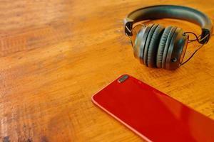 hörlurar och smartphone på träbord. foto