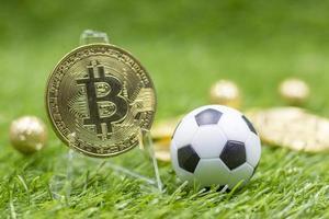 bitcoin med fotboll på grönt gräs bakgrund foto