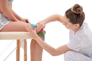 manuell, fysio- och kinesioterapi som utförs av kvinnlig sjukgymnast på en träningsplastik och en kvinnlig patient foto