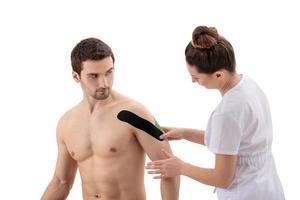 kvinnlig sjukgymnast som sätter på kinesiotejp på patientens axel foto