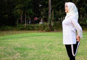 ung muslimsk kvinna som gör muskelsträckning innan hon gör yogarörelser foto