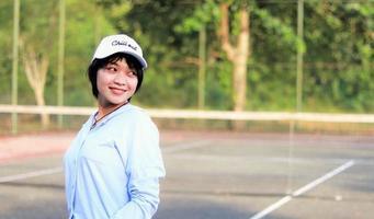 vacker asiatisk kvinna med kort hår, hatt och ler bredt på tennisbanan foto