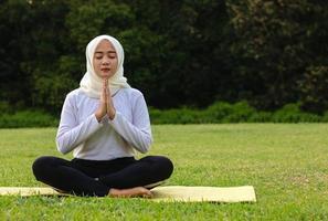 ung asiatisk muslimsk kvinna som sitter på gräset och njuter av meditation foto