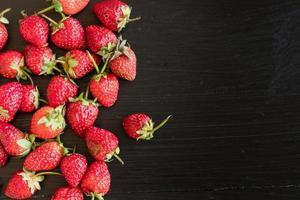 färska jordgubbar på svart trä vintage bakgrund foto