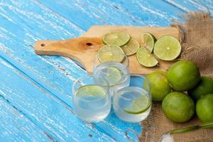 limefruktsaft och citron på ett blått träbord foto