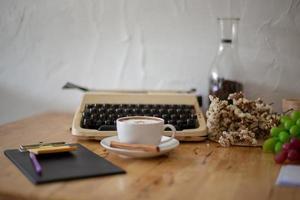 vintage skrivmaskiner och kopp kaffe på träbord foto