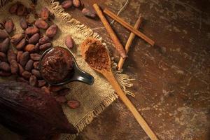 kakaobönor och kakaosnibbar på rustik träbakgrund foto